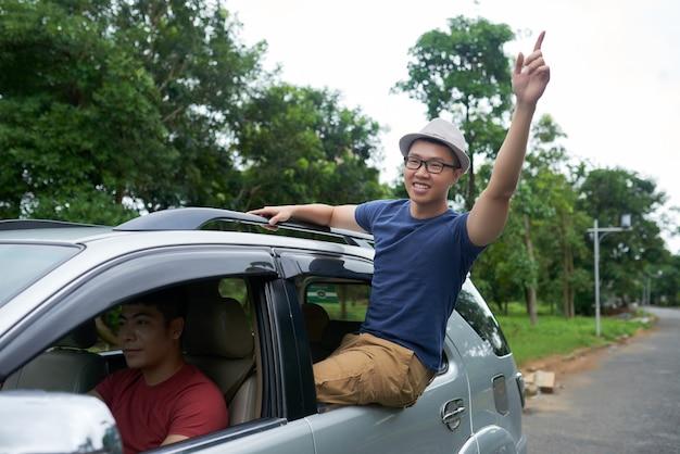 Aziatische mensen drijfauto en vrolijke vriendenzitting in venster van achterdeur Gratis Foto