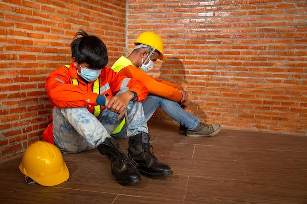 Aziatische mensen stopzetting van de bouwwerkzaamheden als gevolg van de uitbraak van de ziekte van coronavirus 2019 of covid-19. concept van economische crisis, werkloosheid bouwvakker. Premium Foto
