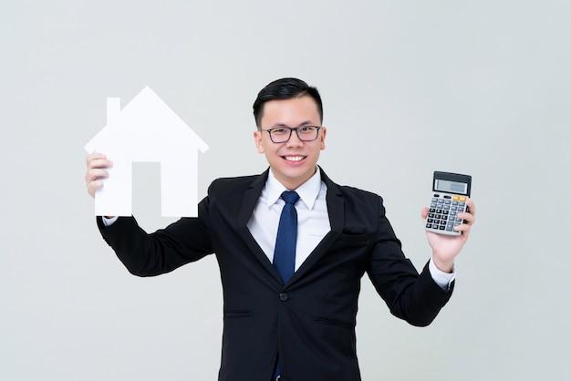 Aziatische mensenagent die huismodel met calculator tonen Premium Foto