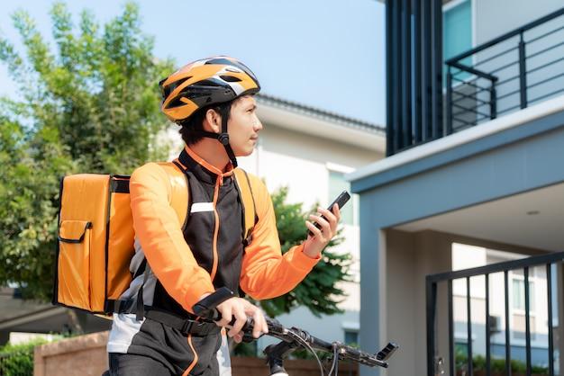 Aziatische mensenkoerier die klantenadres in kaart in telefoon controleren op fiets die voedsel in stadsstraten leveren met een hete voedsellevering van afhaalrestaurants en restaurants aan huis. Premium Foto
