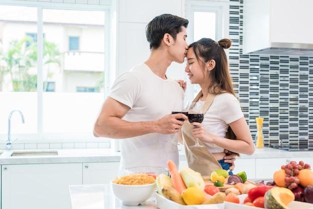 Aziatische minnaars of paren die voorhoofd en het drinken wijn in keukenruimte thuis kussen Premium Foto