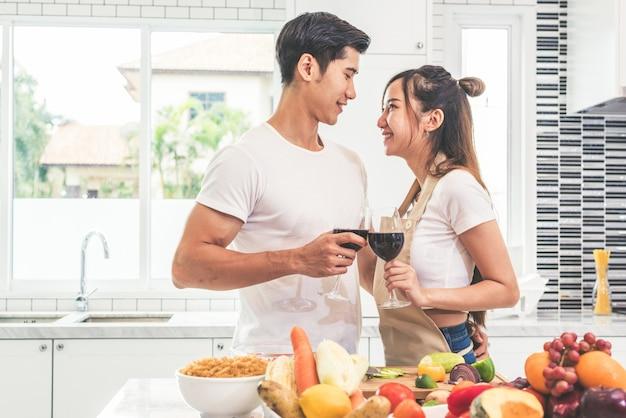 Aziatische minnaars of paren die wijn in keukenruimte thuis drinken Premium Foto