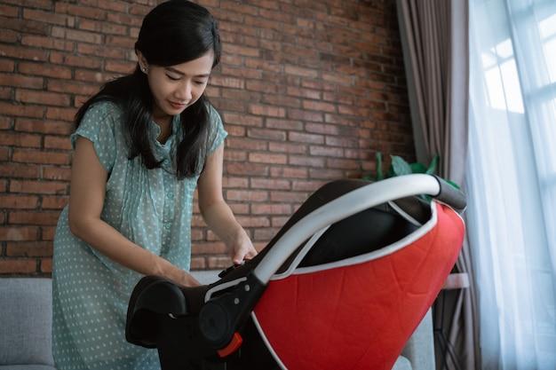 Aziatische moeder die baby zet in zetel Premium Foto