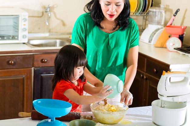 Aziatische moeder en dochter thuis in keuken Premium Foto