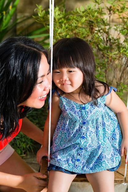 Aziatische moeder en dochter thuis in tuin Premium Foto