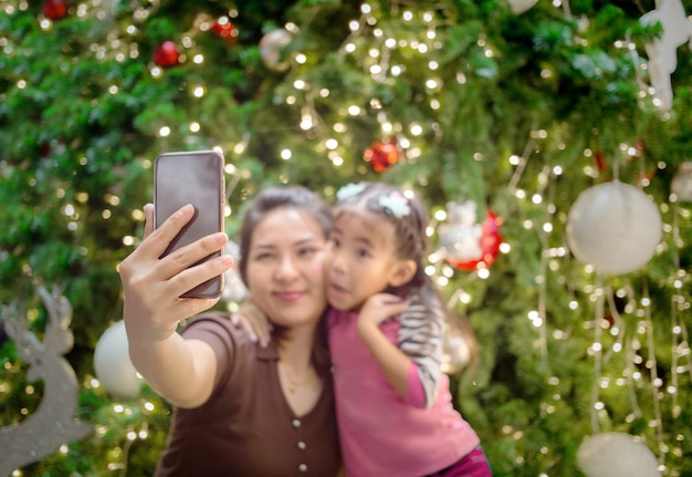 Aziatische moeder hand houden mobiel met dochter om selfie foto te nemen Premium Foto
