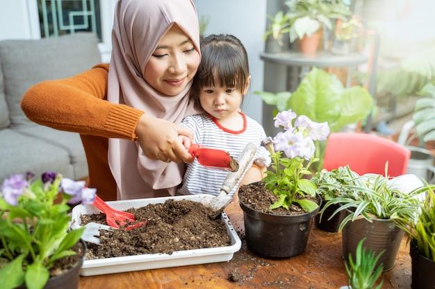 Aziatische moeder helpt haar dochter een kleine schop gevuld met aarde vast te houden om potplanten te laten groeien Premium Foto