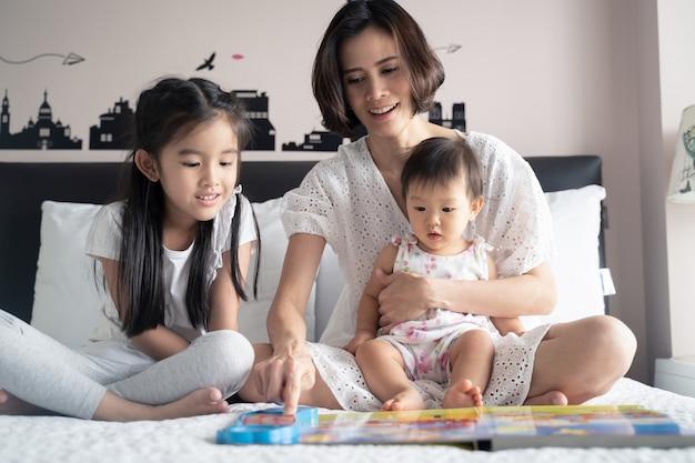 Aziatische moeder muziekboek lezen aan hun dochters zittend op het bed. Premium Foto
