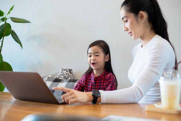 Aziatische moeders leren hun dochters thuis een boek te lezen en notitieboekjes en technologie te gebruiken voor online leren tijdens schoolvakanties. educatieve concepten en activiteiten van het gezin Premium Foto