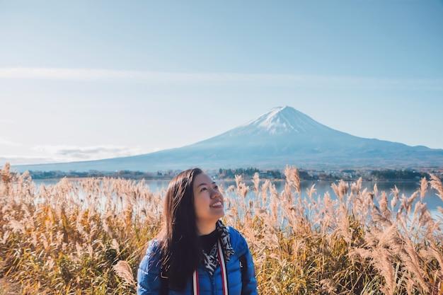 Aziatische mooie glimlachende vrouwentoeristen reizen en voelen zich gelukkig op het gebied van droog gras Premium Foto