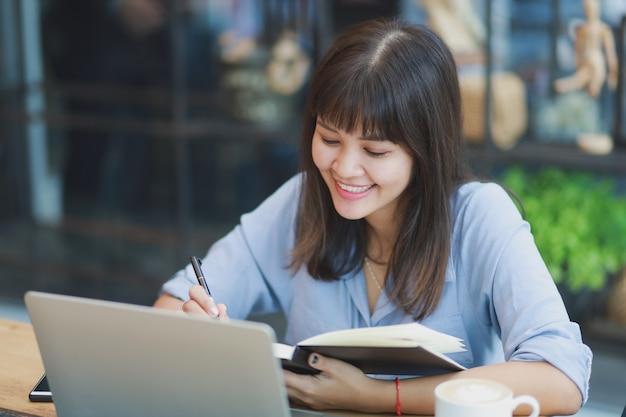 Aziatische mooie vrouw in blauw shirt met behulp van laptop en koffie drinken Premium Foto