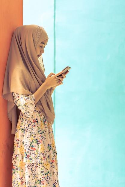 Aziatische moslimstudent gebruikt mobiele telefoon Premium Foto