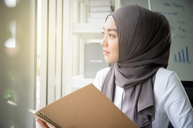 Aziatische moslimvrouw die een boek in bureau leest. het moderne concept van de moslimmensenlevensstijl, het portret van moslim. Premium Foto