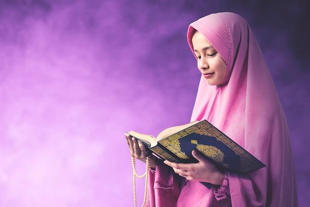 Aziatische moslimvrouw in een sluier die gebedparels houdt en de koran met een gekleurde achtergrond leest Premium Foto