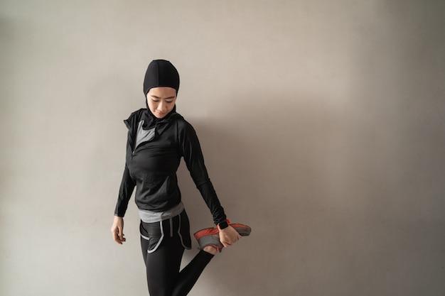 Aziatische moslimvrouwen die hijabsportkleding dragen die benen het uitrekken doen zich Premium Foto