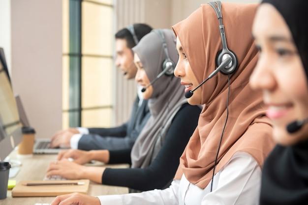 Aziatische moslimvrouwen die in call centre met team werken Premium Foto