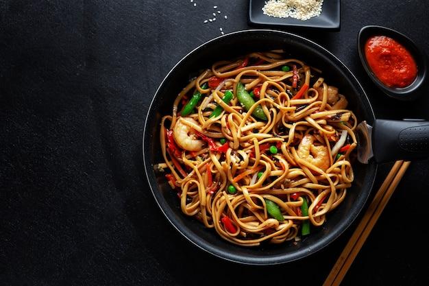 Aziatische noedels met garnalen en groenten die op pan op donkere achtergrond worden gediend. Premium Foto
