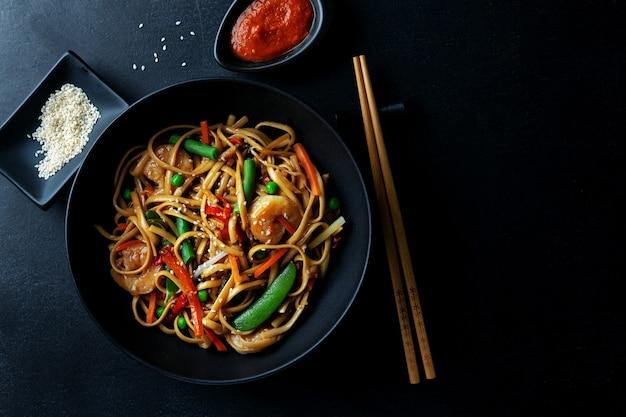 Aziatische noedels met garnalen en groenten geserveerd in kom op donkere achtergrond. Premium Foto