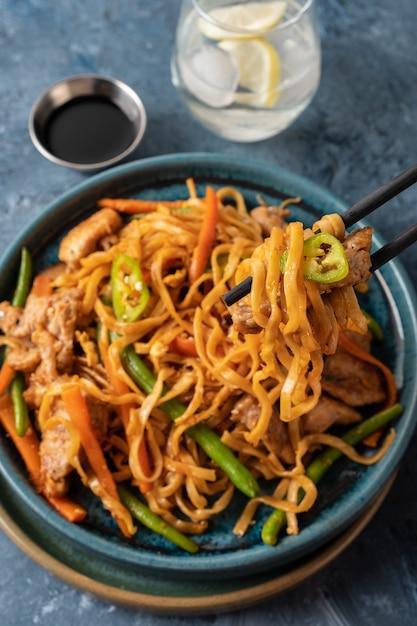 Aziatische noedels met varkensvlees in teriyakisaus, met sperziebonen, wortelen en shiitake paddenstoelen. Premium Foto