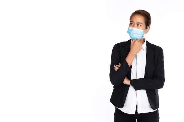 Aziatische onderneemster die chirurgisch gezichtsmasker in zwart kostuumjasje draagt stelt als denken Premium Foto