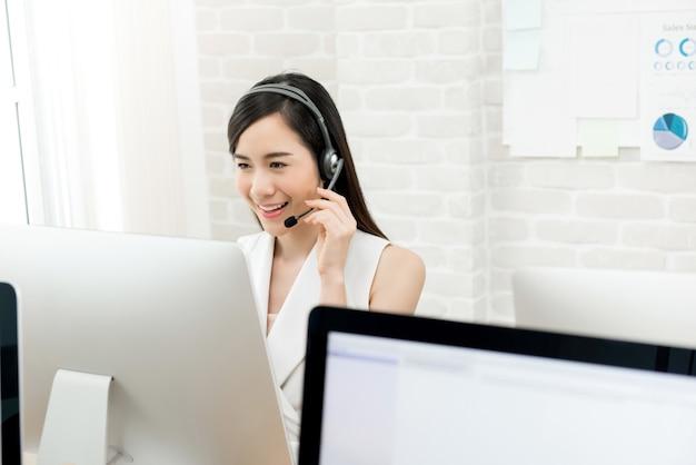 Aziatische onderneemster die hoofdtelefoon draagt die in call centre werkt Premium Foto