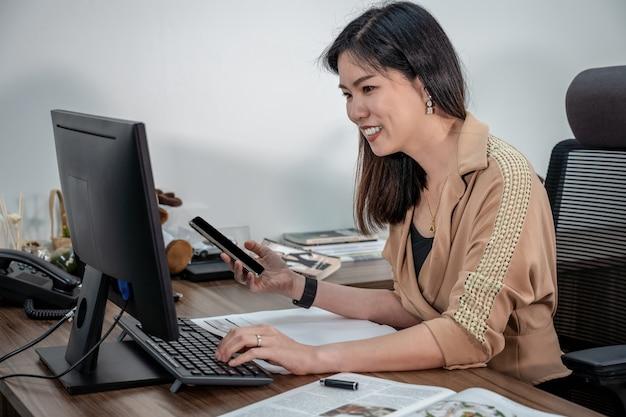 Aziatische onderneemster die in formeel kostuum en met computer en mobiel in bureau, bedrijfs en projectplan schrijven voor het concept van de klantendienst Premium Foto