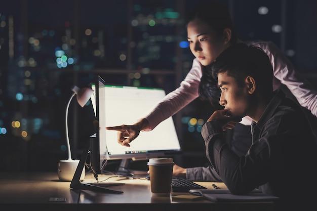 Aziatische onderneemster en zakenman die laat hard samen met technologiecomputer werken in bureau Premium Foto