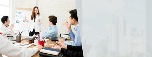 Aziatische onderneemsterleider die het werk in een vergadering met haar collega's, bannerachtergrond voorstelt Premium Foto