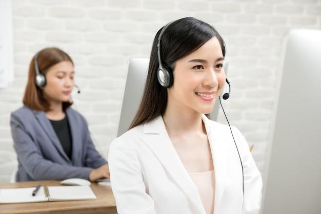 Aziatische onderneemsters die hoofdtelefoons dragen Premium Foto