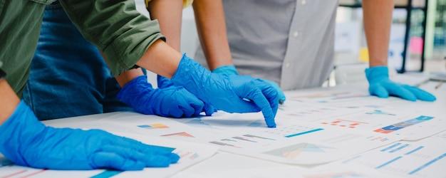Aziatische ondernemers bespreken zakelijke brainstormvergadering samen delen gegevens, dragen gezichtsmasker en handschoen weer aan het werk in een nieuw normaal kantoor. levensstijl en sociale afstand nemen na het coronavirus. Gratis Foto
