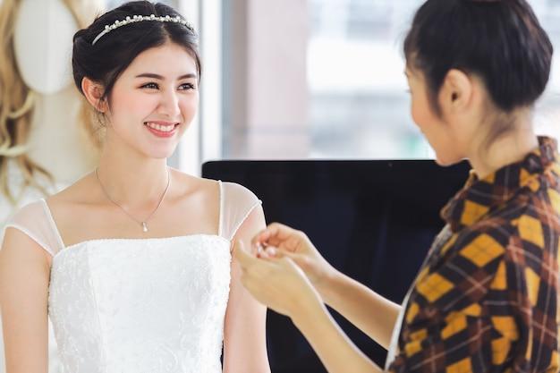 Aziatische ontwerper die in de opslagwinkel van de huwelijksmode werkt Premium Foto
