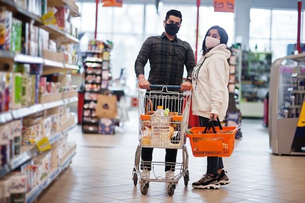 Aziatische paar dragen in beschermend gezichtsmasker samen winkelen in de supermarkt tijdens pandemie. Premium Foto
