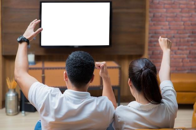 Aziatische paar televisiekijken op de bank Premium Foto