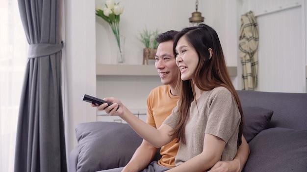 Aziatische paar tv kijken en het drinken van warme kop koffie in de woonkamer thuis, zoete paar genieten Gratis Foto