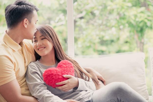 Aziatische paren die op de bank zitten waarin vrouwen een rood hart houden en gelukkig glimlachen. Premium Foto