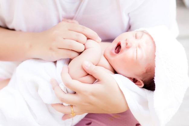Aziatische pasgeboren in de arm van de moeder na het hebben van een bad Premium Foto