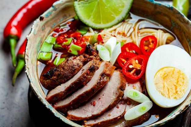 Aziatische pittige ramen noodles met varkensvlees, ei en groenten in blauwe kom Premium Foto