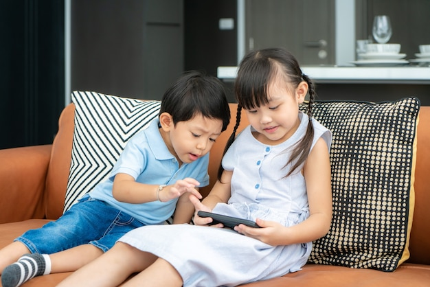 Aziatische schattig broer of zus kind met behulp van een smartphone Premium Foto