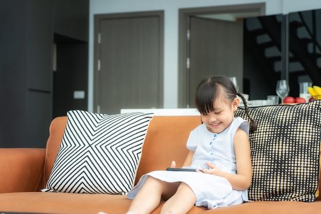 Aziatische schattig kind met behulp van een smartphone Premium Foto