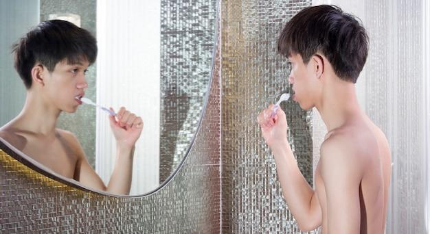Aziatische schattige jongen hun tanden poetsen voor de spiegel in de ochtend. Premium Foto