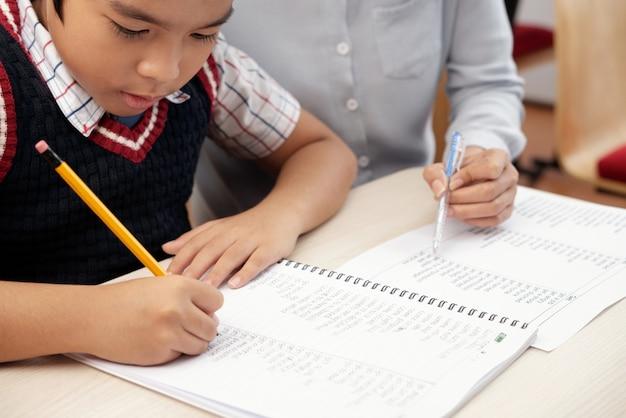 Aziatische schooljongen schrijven in notitieblok en onherkenbare vrouw zitten en kijken Gratis Foto