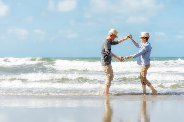 Aziatische senior paar dansen op het strand. helder huwelijksreis samen heel geluk na pensionering. plan levensverzekering. activiteit na pensionering in de zomer Premium Foto