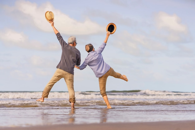 Aziatische senior paar springen op het strand. kennelijk huwelijksreis samen heel geluk na pensionering. plan levensverzekering. activiteit na pensionering in de zomer Premium Foto