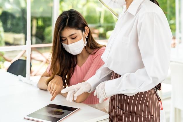 Aziatische serveerster draagt gezichtsmasker en gezichtsscherm met behulp van tablet om het elektronische menu van het restaurant te tonen Premium Foto