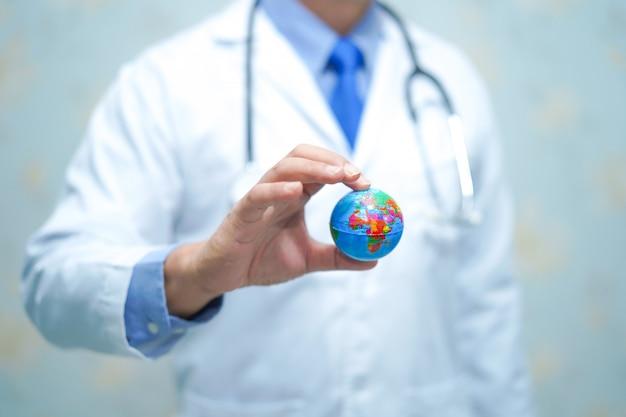 Aziatische slimme mens arts die een bol houdt: gezond sterk medisch concept. Premium Foto