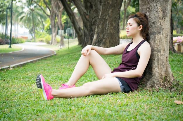 Aziatische sport vrouw rust op grasland in park na het lopen Premium Foto