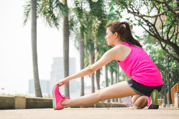 Aziatische sport vrouw warming-up voor hardlopen en yoga in park Premium Foto