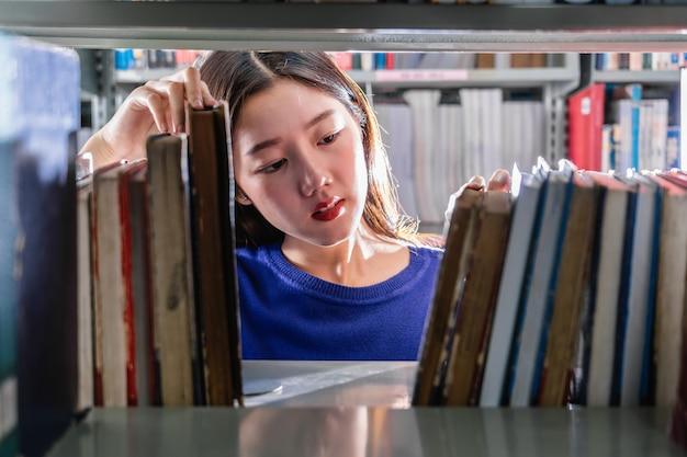 Aziatische student die in toevallig kostuum het boek in ernstig gevoel van boekenplank zoeken in bibliotheek van universiteit Premium Foto