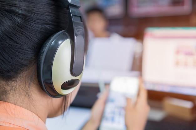 Aziatische studente die op smartphone en computerpc leren voor het letten van video op tutorial met hoofdtelefoons Premium Foto