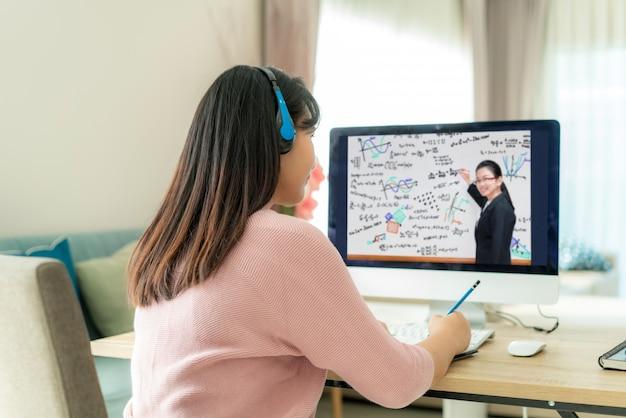 Aziatische studente videoconferentie e-leert met leraar op computer in woonkamer thuis. Premium Foto